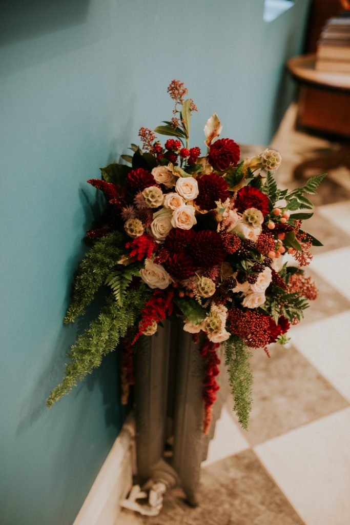 A huge bouquet of red and cream flowers with lots of greenery sits on top of an old 1920's cast iron radiator
