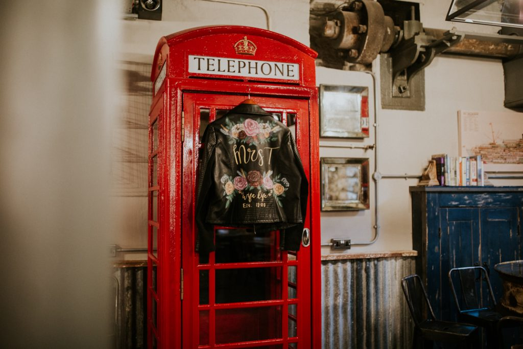 Brides black leather hand painted jacket hangs on a red telephone box at Holmes Mill