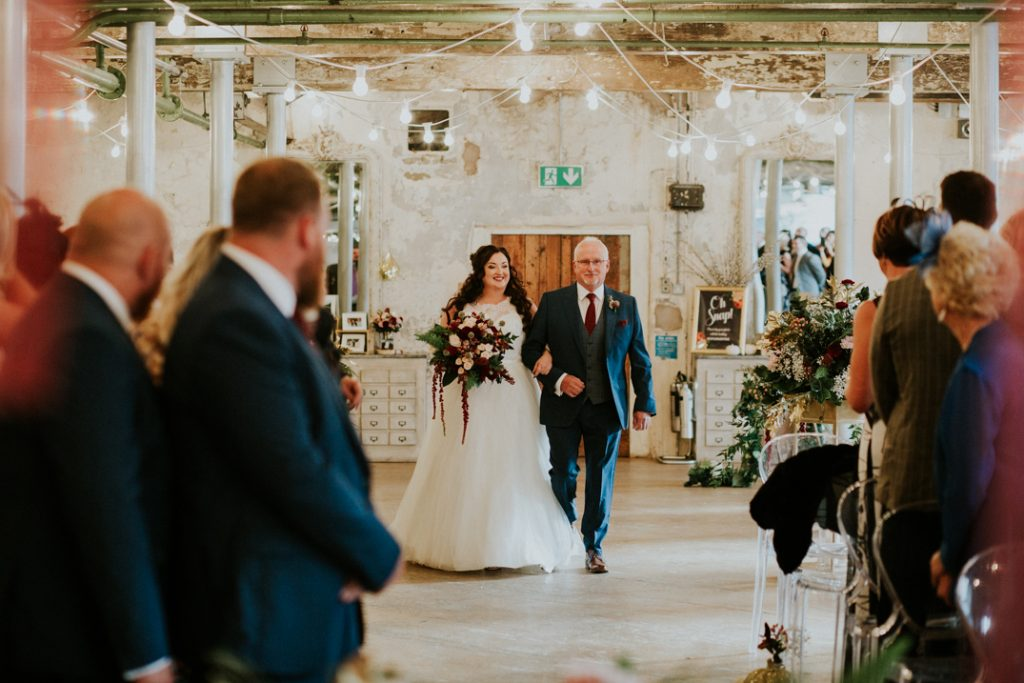 Bride walks down the aisle in the main hall at Holmes Mill