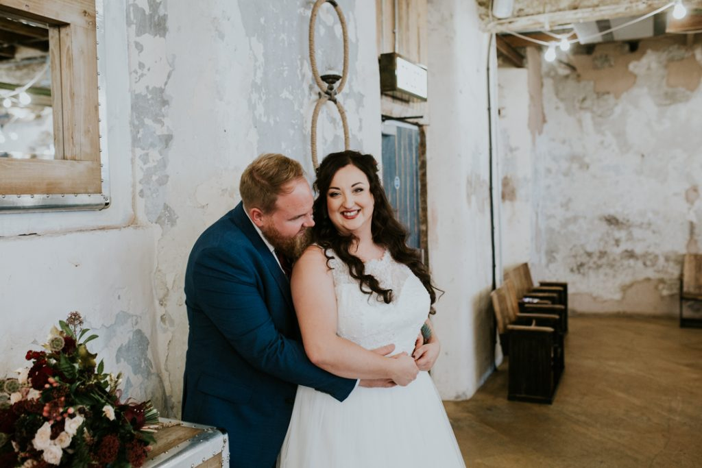 Bride and groom lean against a wall in Holmes Mill whilst laughing and looking at the camera