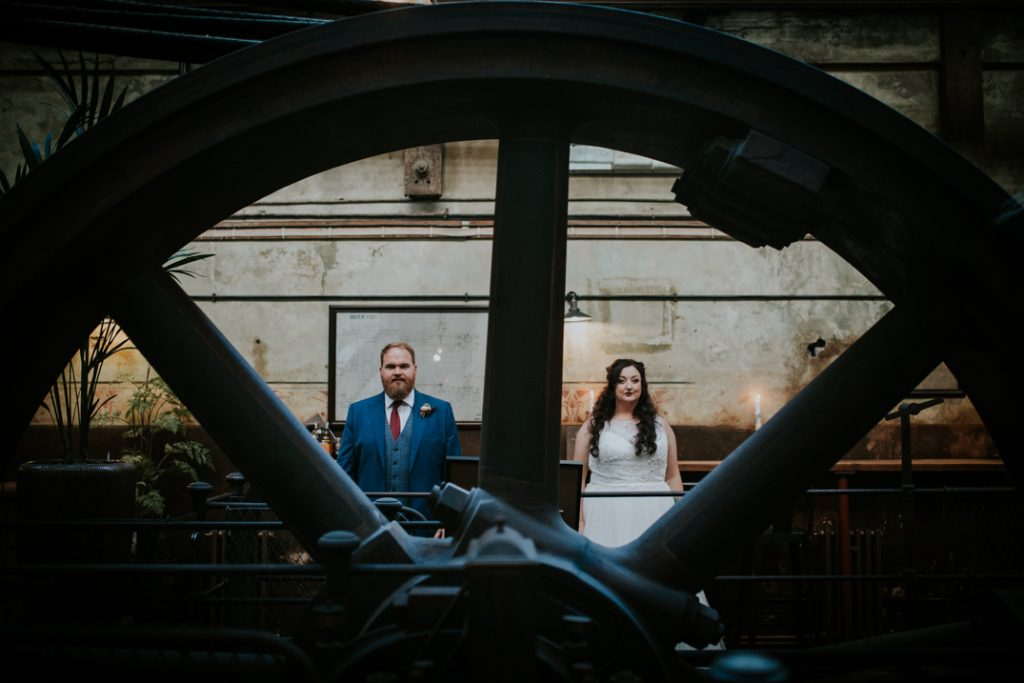 Bride and groom stand in the engine room at homes mill, they placed behind the old mill wheel looking through sections of the wheel