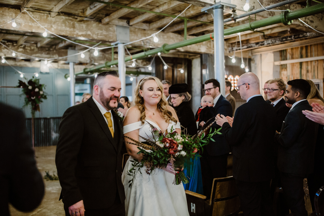 Holmes Mill Wedding Photography Bride and groom walking down the aisle bride is holding her bouquet by Wildfire floral co