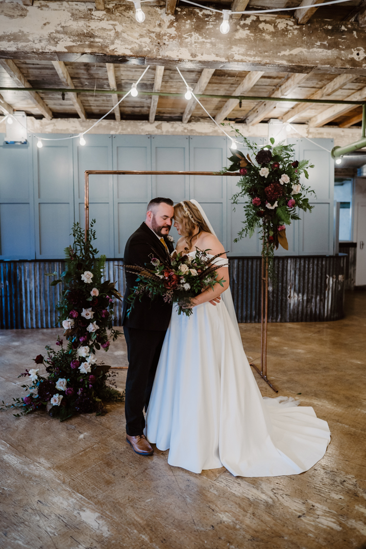 Bride and groom pose under a flower arch ay Holmes Mill They embrace and have their first kiss Holmes Mill Wedding Photography