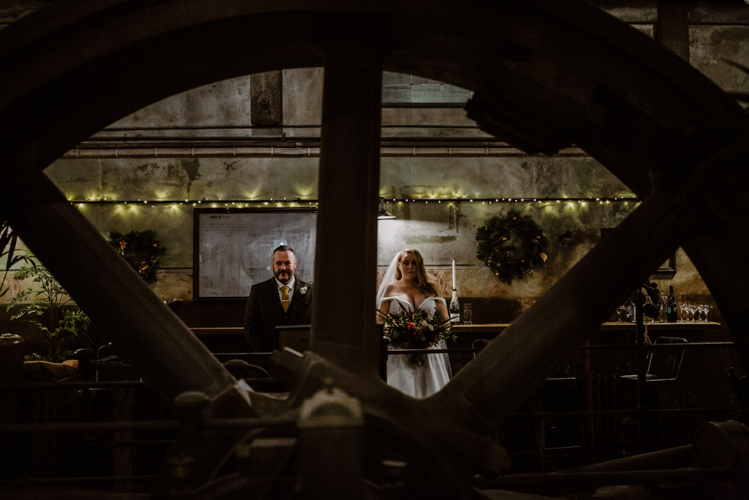 Bride and groom stand for portraits in the engine room at holmes Mill
