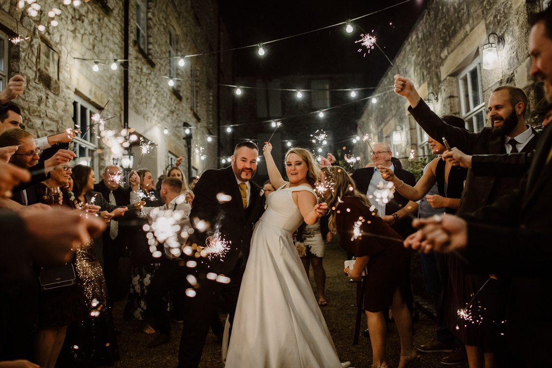 Bride and groom along with guests stand next to the spinning block at holmes Mill with sparklers