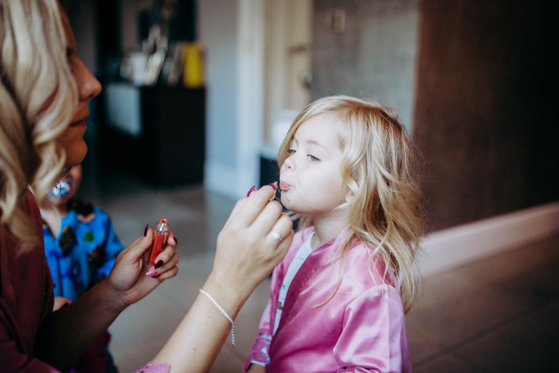 bridesmaid applying lipstick